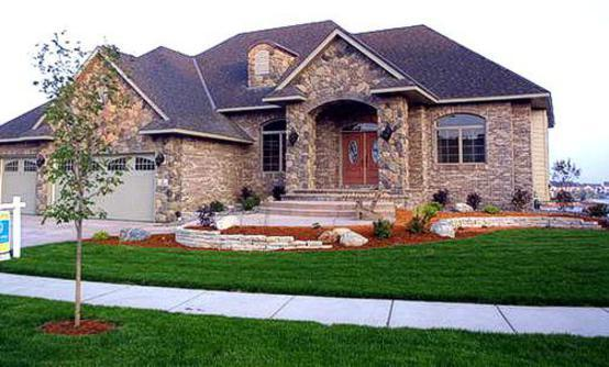 Beautiful modern stone home with a beautiful green healthy lawn utilizing our lawn aeration packages
